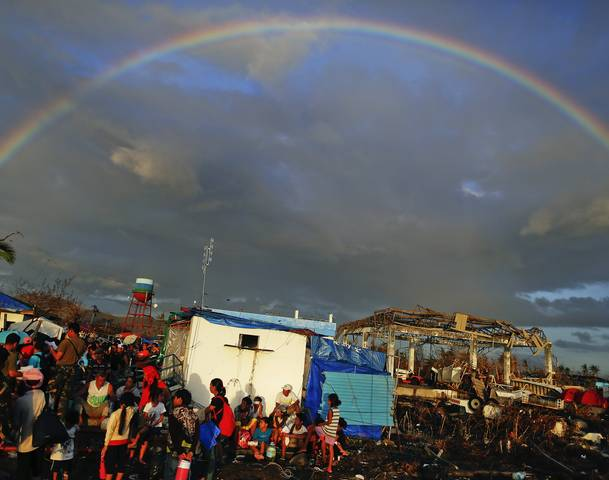 A rainbow appears above Typhoon Haiyan survivors desperate to catch a flight from the Tacloban airport