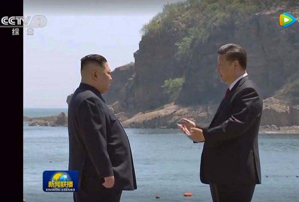 中国・大連で海をバックに談笑する習近平国家主席(右)と北朝鮮の金正恩朝鮮労働党委員長=8日の中国中央テレビから(時事)