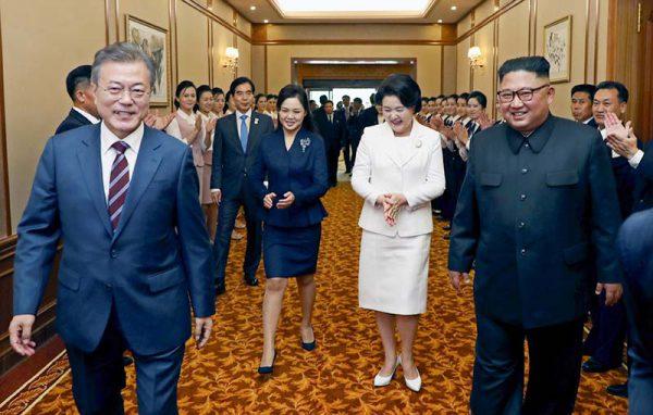 18日、平壌の百花園迎賓館に到着し、談笑しながら歩く韓国の文在寅大統領(左)と北朝鮮の金正恩朝鮮労働党委員長(右)(EPA時事)