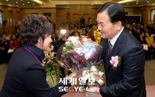 20日、ソウル龍山区の世界平和統一家庭連合の大講堂で開かれた韓国宗教協議会の会長が·就任式のイベントで、第20代会長を務める世界平和家庭連合ユギョンソク会長(右)が妊婦姫韓国の宗教の女性協議会副会長からのお祝いの花束を受けてている。 ギムボムジュン記者